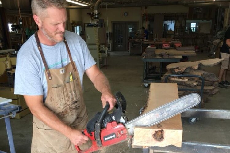 Gary Keener, co-owner of Keener & Schultz Fine Woodworks, cuts a piece of wood for a piece of furniture. The shop's Facebook page features their handmade work from start - as tree trunks - to finished designer furniture.